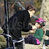 Maggie Gyllenhaal checks Ramona Sarsgaard's bike helmet before taking off.