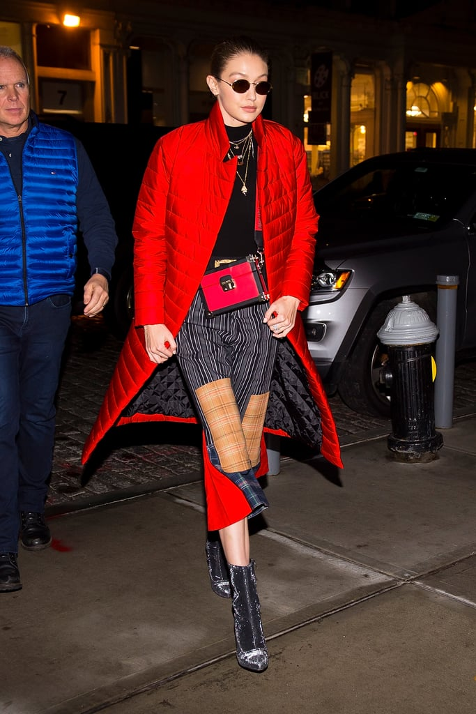 Styling a pair of PJ-style pants with a Tommy x Gigi handbag and a cherry red puffer to match. She finished her look off with custom Stuart Weitzman Clingy boots.