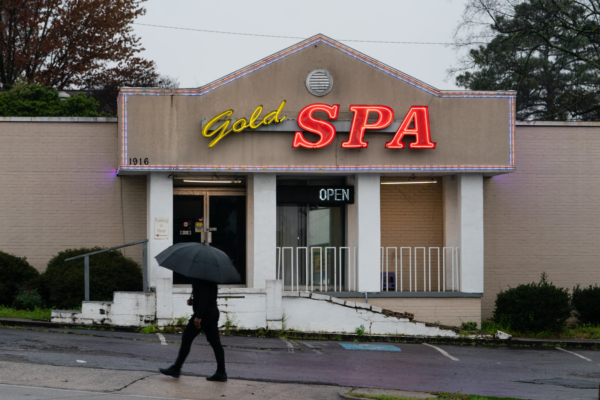 ATLANTA, GA - MARCH 17: A man walks past a massage parlor where three women were shot and killed on March 17, 2021 in Atlanta, Georgia. Suspect Robert Aaron Long, 21, was arrested after a series of shootings at three Atlanta-area spas left eight people dead on Tuesday night, including six Asian women. (Photo by Elijah Nouvelage/Getty Images)