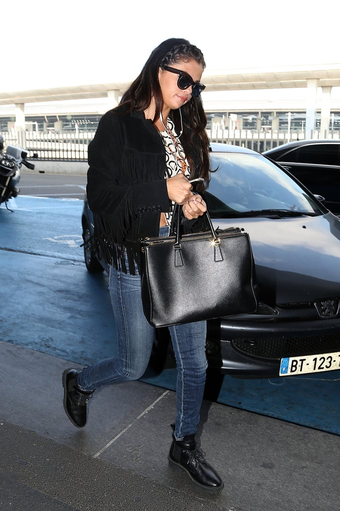 Fall staple: a fringed suede jacket by Saint Laurent. Selena wore it with: a Louis Vuitton bubble top, DKNY skinnies, a Prada bag, and Balenciaga ankle boots in Paris in October 2014.