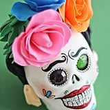 How adorable is this Frida Kahlo sugar-skull variation, complete with fake roses in her hair?
