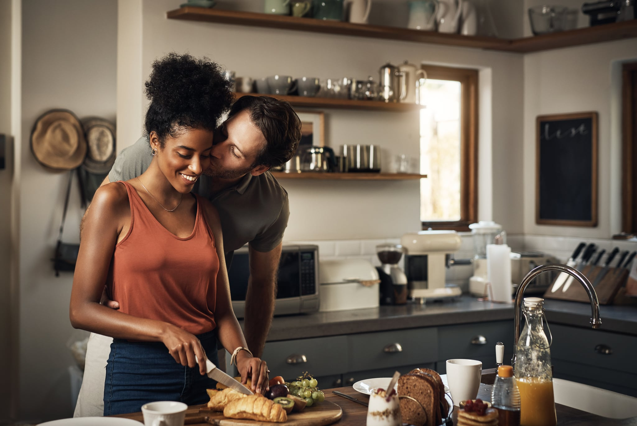 Cropped shot of an affectionate middle aged man kissing his wife on the cheek while she prepares breakfast in their kitchen at home