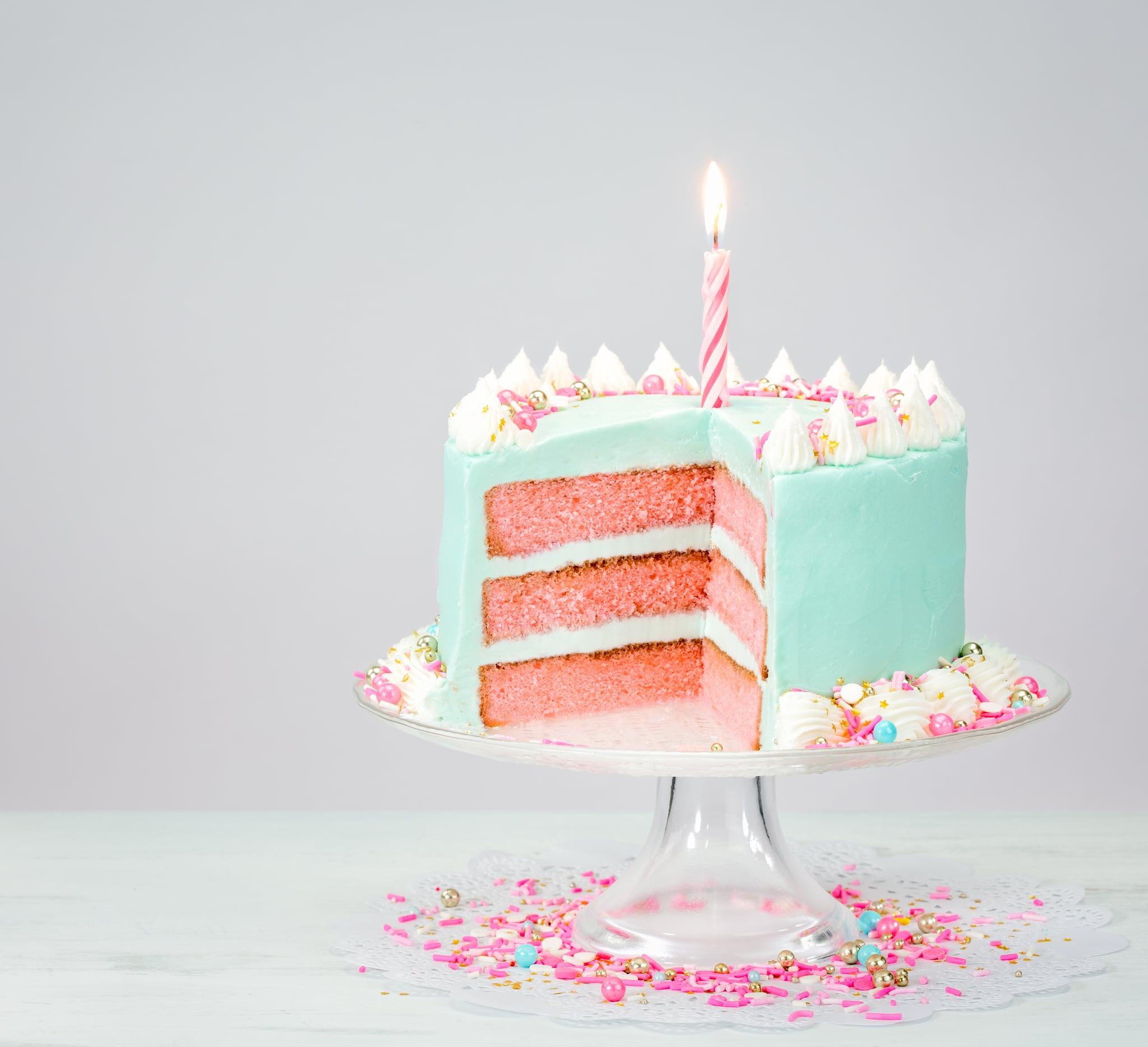 Pastel blue birthday cake over white background with pink layers and sprinkles.