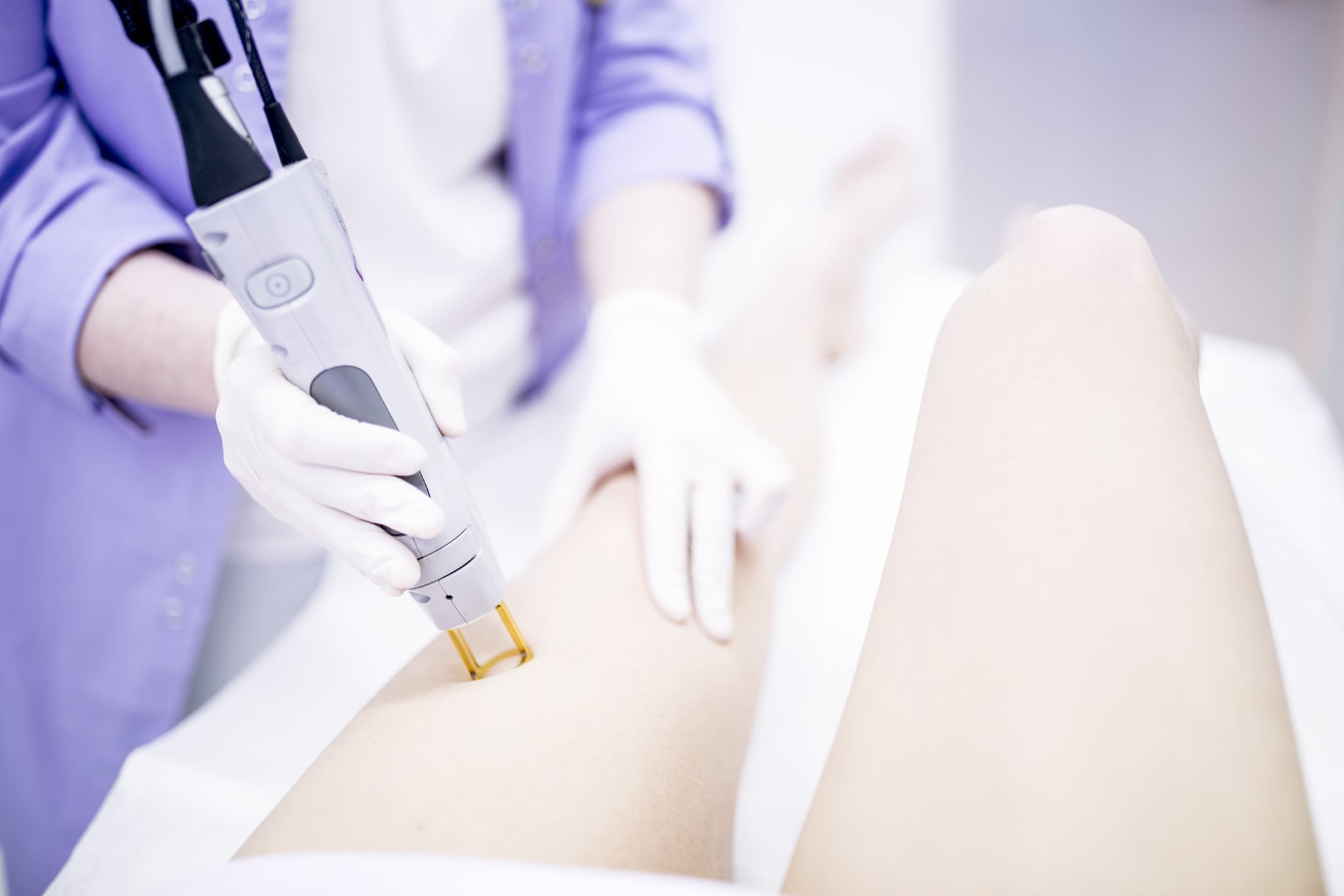 Young woman getting laser hair removal treatment on leg, close-up.