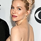 A side view of the top of her strapless dress and her matching makeup.