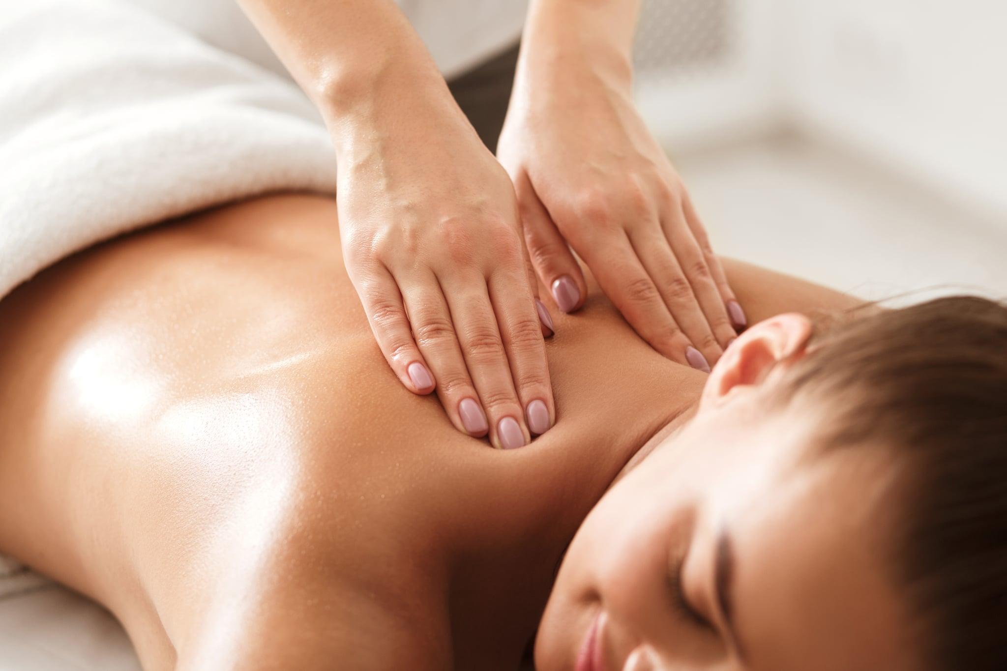 Young woman enjoying therapeutic neck massage in spa centre, closeup