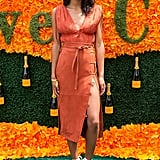 Wearing an orange dress that featured a thigh-high split. Laura finished her ensemble off with white lace-up espadrilles.