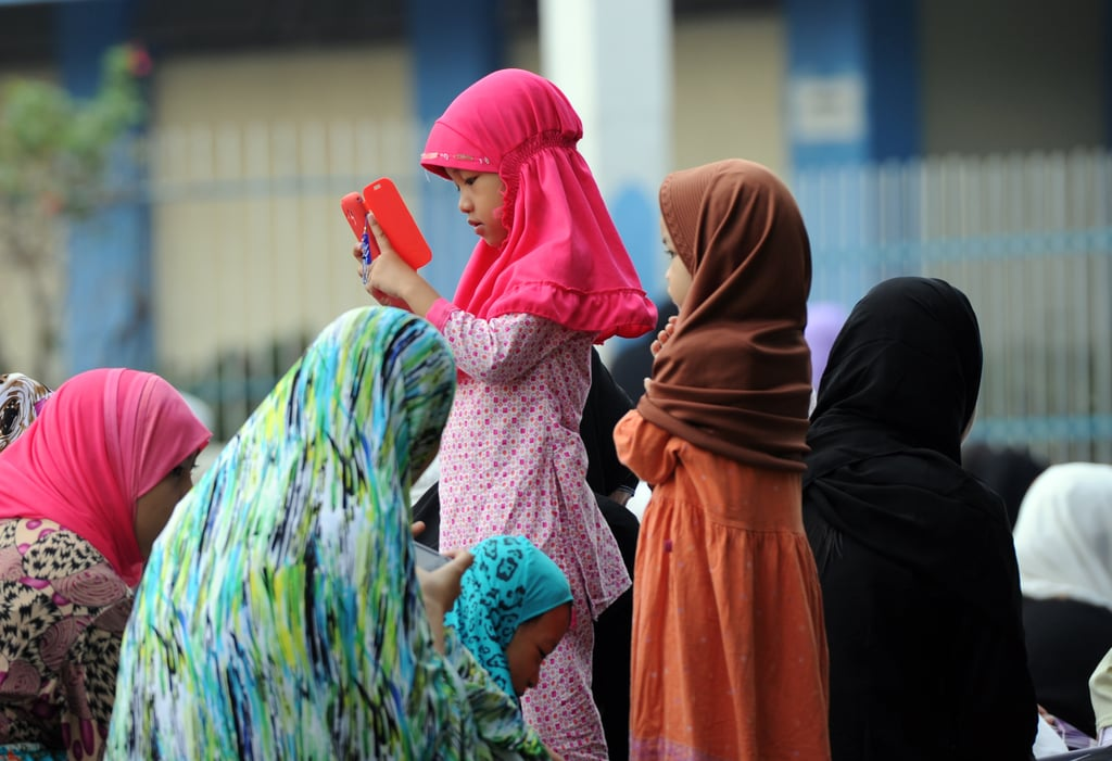 A young girl played with her mother's phone during the Eid al-Fitr festival in the Philippines.