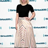 In May, she kept things simple in a black top and striped midi skirt.