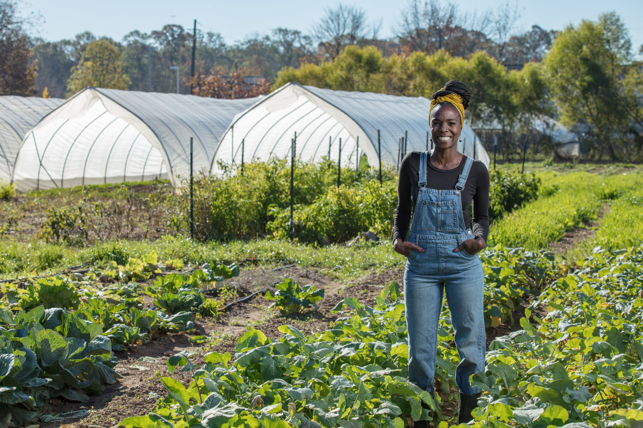Host Jamila Norman poses with crops at a farm in Atlanta, as seen on Homegrown, Season 1.