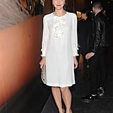 Maggie Gyllenhaal wore a white silk ruffled dress, grey crystal drop earrings, python platform heels, and black and a white watersnake framed clutch to the party.