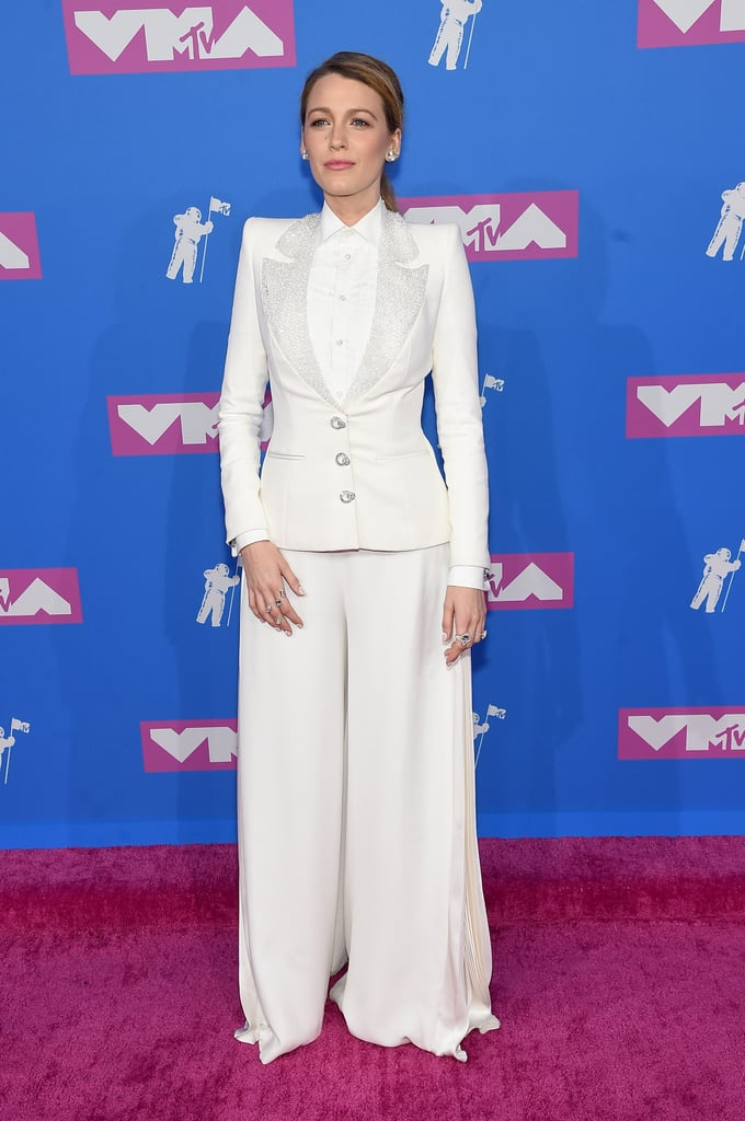 May I have your attention, please? Blake Lively's 2018 MTV VMAs ensemble deserves a second look. The 30-year-old actress waltzed onto the  pink carpet on Aug. 20, decked out in the most unexpected outfit: a white flowing suit with sparkling lapels and a high-neck button-up top. While other attendees were donning naked dresses, Blake took a more modest route with her monochrome outfit.  She's been on quite a fashion spree lately while promoting her upcoming film, A Simple Favour. Think this could be a nod to her stylish and  mysterious character, Emily? Check out more snaps of Blake's sophisticated look ahead, from all angles.