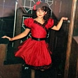 """My mom made me amazing Halloween costumes, most of them reflecting significant moments in fashion history: a poodle skirt, a flapper dress, and this can-can girl costume, which was probably my favorite. She altered an old red dress of hers to fit me, added lace and sequin trim, and layered it over a petticoat. My favorite part of the costume was the fishnet stockings. My favorite thing about this photo is my pose."" — Nancy Einhart, VP and executive editor"