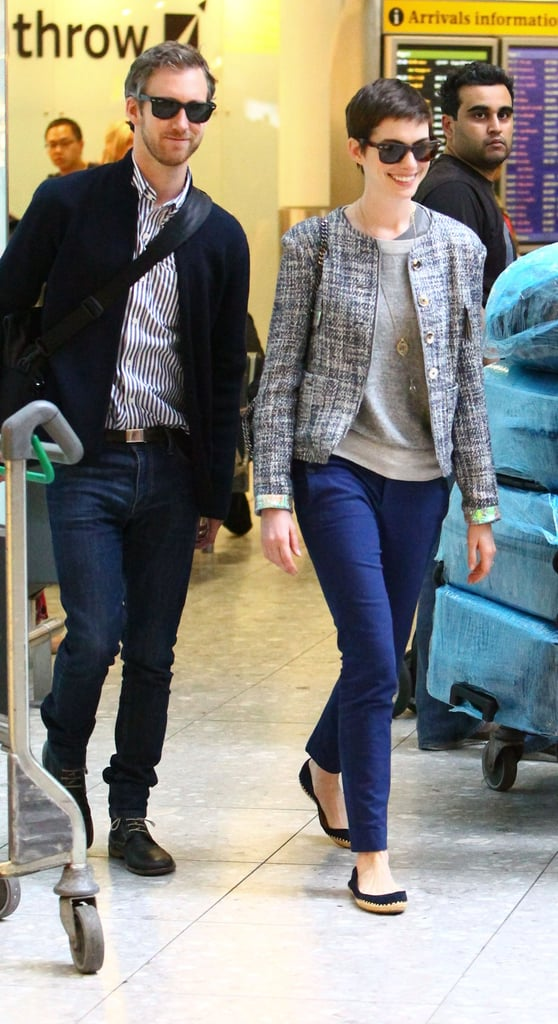 Anne Hathaway and Adam Shulman stepped off a plane and into London's Heathrow Airport this morning. The couple are overseas to continue promoting Anne's The Dark Knight Rises, which opens in the US Friday. She's due to attend the London premiere this evening, along with her other costars Christian Bale and UK native Tom Hardy. The Batman gang was just together in NYC for the US premiere of The Dark Knight Rises. For the occasion, Anne wore a revealing white Prabal Gurung gown. Her leading lady Marion Cotillard struck a similar style note, wearing a Dior creation in a similar hue. We'll soon see what Anne decides to wear to the next red carpet event, but one thing she'll definitely sport is the Kwiat engagement ring Adam presented her with back in November of last year.