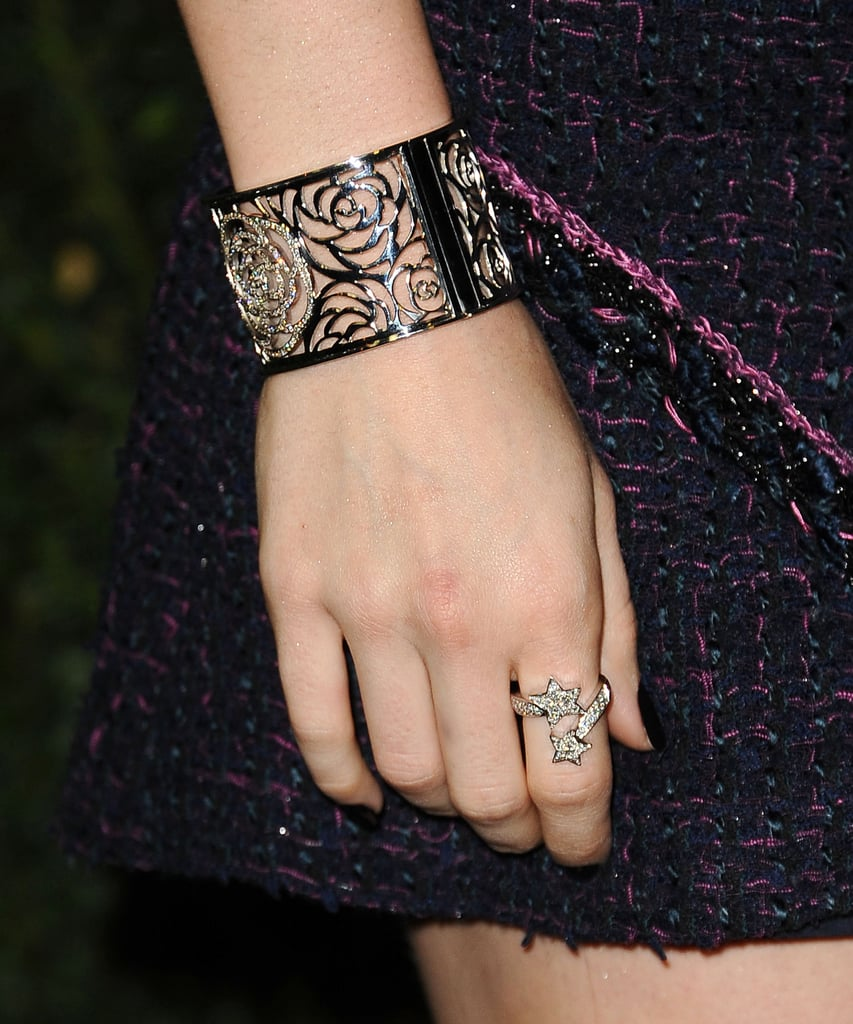 Lily Collins styled her tweed shorts suit with a Camellia Ajoure cuff and a Camellia Ajoure star ring, both by Chanel.