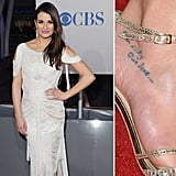 "Lea Michele has two tattoos on her right foot — one is a butterfly that was drawn by her cousin and the other reads ""our city, our love."""