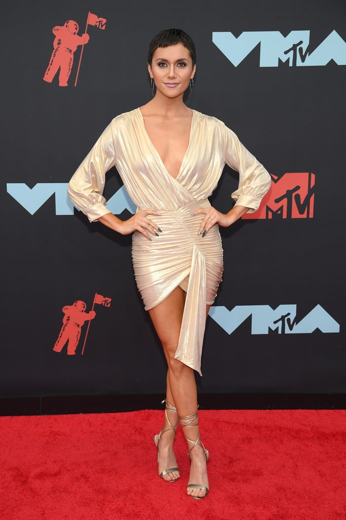 Alyson Stoner made headlines for her performance with Missy Elliott during Monday night's MTV VMAs, but the gorgeous gold dress she wore on the red carpet deserves just as much attention.  The 26-year-old dancer showed up to the event in a metallic minidress with matching gladiator-style heels, giving her an overall goddess-like appearance. This is a far cry from the bright yellow Adidas tracksuit she wore on stage but honestly, we'd happily wear both on any given day. Alyson tied her glam red carpet look together with large silver hoop earrings, delicate rings, and multicolored nail polish. How chic!  Keep reading to see Alyson's fierce award show look from all angles.