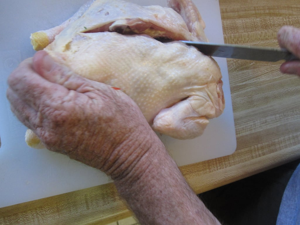 With a sharp, strong knife, make an incision into the chicken to the right of the backbone. Slice downward (you will hear a crunching noise as you break through the bones), cutting all the way through the chicken.