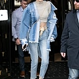 This denim on denim look is infinitely more interesting thanks to Gigi's crop top, two-tone jeans, and distressed jacket.