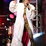 Miley Cyrus sparkled in a gold crop top and trousers (topped off with a gigantic white fur coat, of course) to perform in Times Square.