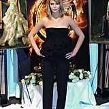 Jennifer Lawrence joined her Hunger Games cast for their morning photocall in a polished but playful tiered strapless top and trousers, both by Dior, which she finished with a bright pop of color on her heels.