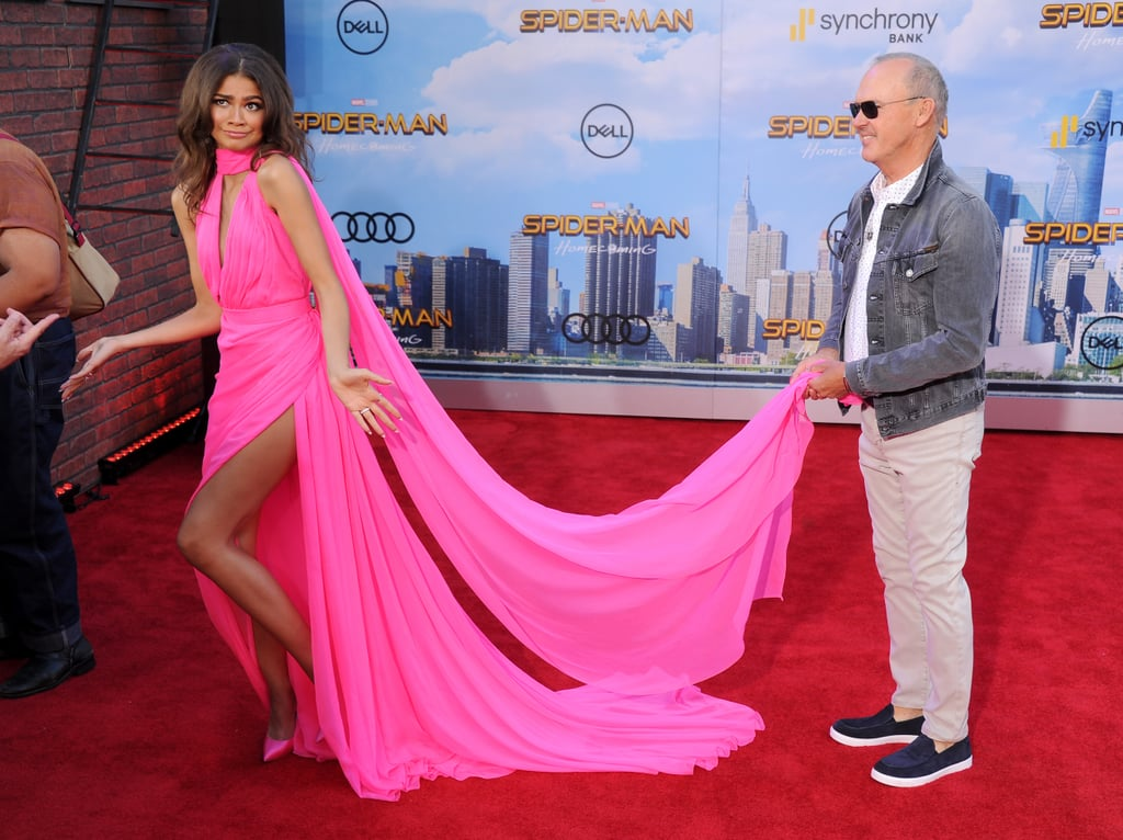 In case you missed it, Zendaya absolutely slayed while walking the red carpet at the Spider-Man: Homecoming premiere in LA on Wednesday. The actress looked beautiful as she smiled for photographers in a bright pink dress with a long train. It was so long, in fact, that she actually had to enlist a little help from one of her costars as she made her way inside. Zendaya shared an adorable moment with Michael Keaton, who plays the villain Vulture in the movie, as he held up her gown (seriously, he looked like a proud father sending his daughter off to prom). And this could actually turn out to be pretty fitting since there's a rumor going around that Zendaya's secretive character Michelle is actually Vulture's daughter.