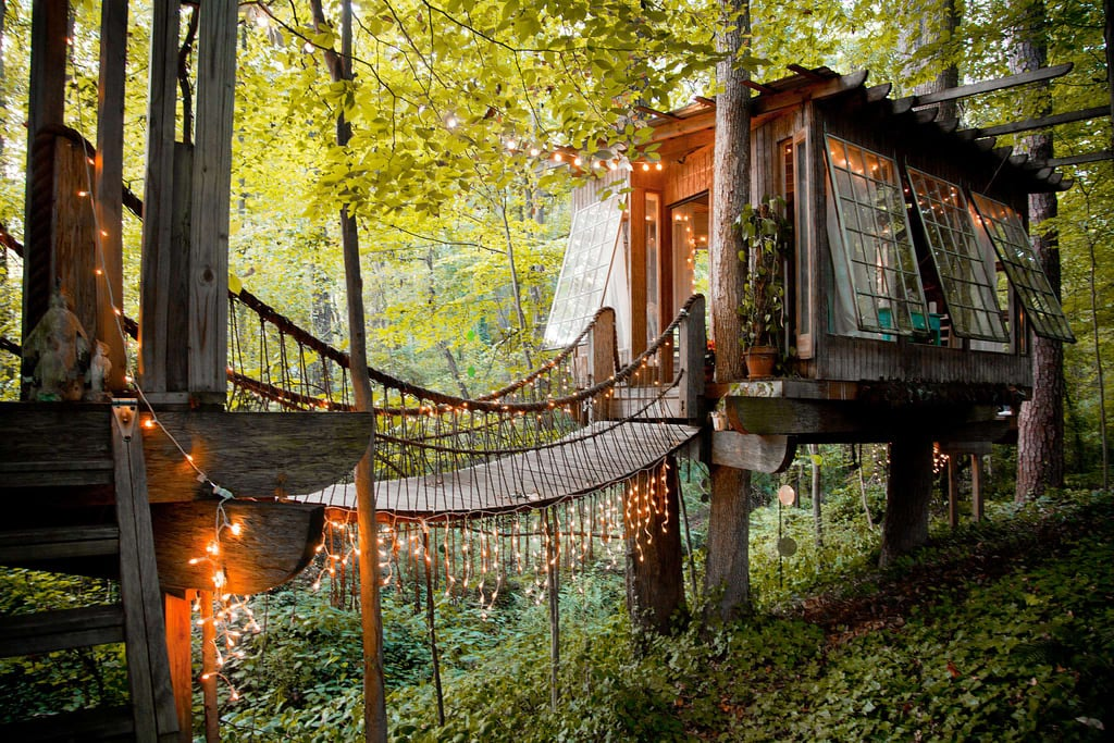 "From sprawling oceanfront manors to eclectic apartments and airstreams, there's no shortage of memorable and conveniently located places to rent from Airbnb. But it turns out that people aren't flocking to book the same homes as their favorite celebrities or even a traditional house at all — the most requested listing is actually a tree house.  The Atlanta tree house is $375 a night and is booked through May 2018. According to Today, the listing gets 300,000 visits each month and 147,052 people have saved it to their Airbnb ""wish list."" Although it doesn't come with a connected bathroom, the Secluded Intown Treehouse offers visitors a memorable experience that outweighs what it lacks in traditional amenities. According to the listing, this urban retreat is minutes from downtown and is a suite of three different rooms nestled in the trees with rope bridges connecting them. ""The tree house provides and intimate, simple and calming retreat for two people,"" the listing states. ""Centrally located within the heart of intown Atlanta, the tree houses are a hidden gem. The subject of numerous TV and magazine features, they are often described as being the most relaxing, romantic, dreamy and unique place you'll ever stay. What could be better than falling asleep in the trees and waking up to birds singing around you — all within the city limits?"" The bedroom boasts organic linens with a bed that can be rolled out onto a platform to sleep under the stars and overlook a calming stream. In the next tree, guests can enjoy a living room filled with antique decor and a picturesque balcony. The third element is a deck that surrounds a 150-year-old tree. Peter Bahouth built the tree house in his backyard 18 years ago, but only first considered renting it out when Airbnb gained popularity. ""I didn't really know how I would feel about having people stay out here. But I began to realize that people were having these amazing, great experiences and it was meaningful [to them], and it therefore became meaningful for me,"" Peter told Today. Many of Peter's guests come for the opportunity to unplug while being immersed in nature. ""People come here and they write and they think,"" Peter said. ""They leave great stories and they have things happen to them here. Sometimes, they leave after two days and they just look different — they look like they just needed to simmer down a little."" Take a look at the photos of the cool rental!"