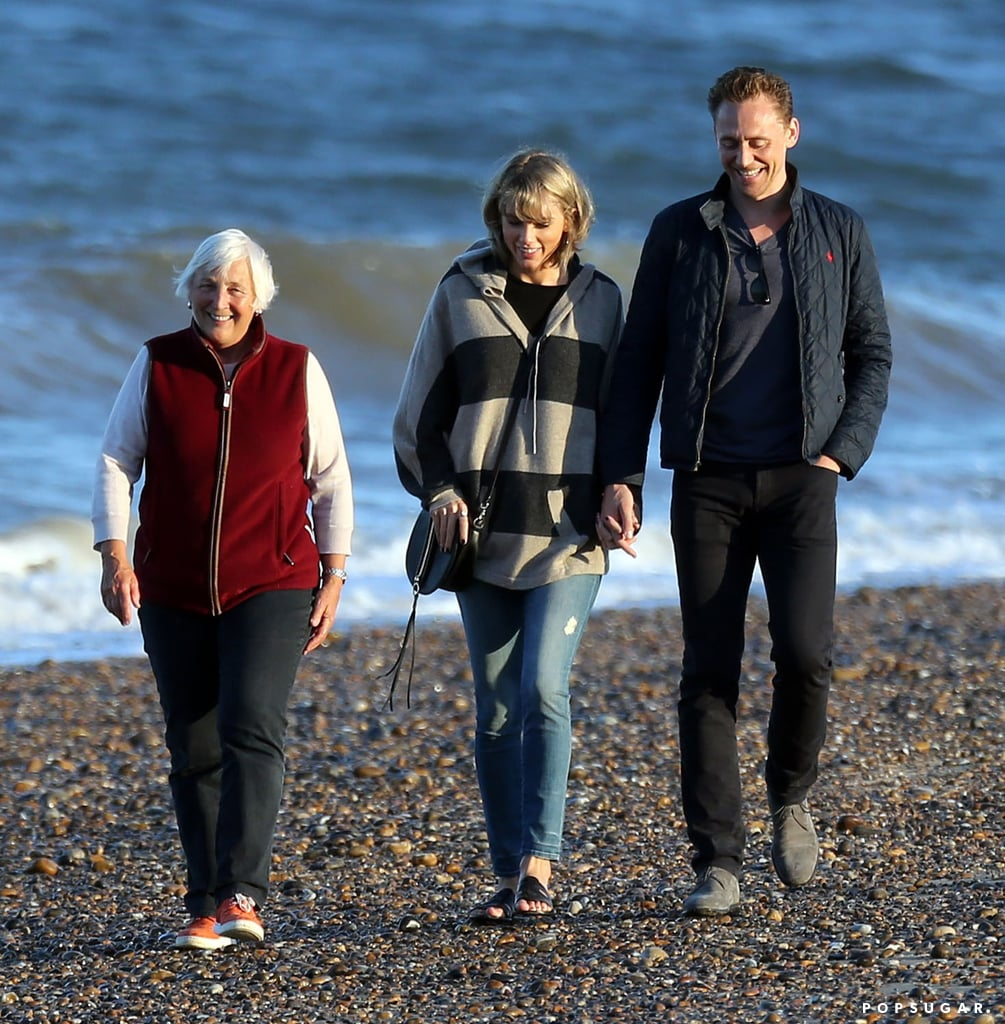 "Taylor Swift and Tom Hiddleston definitely have an affinity for romantic walks on the beach. Not long after being spotted making out near the ocean in Rhode Island, the new couple took a stroll along the water together in the UK on Saturday. This time, though, they weren't alone: Tom's mother, Diana Hiddleston, also joined the lovebirds for the sunset outing and the trio looked smiley and happy while chatting on the sand. Taylor stayed warm in Mother skinny jeans and an oversize striped sweater. On Sunday, the couple was bundled up for another walk on the beach in Suffolk along with Diana and more members of his brood.  Tom and Taylor jetted off to England on Friday; they were seen arriving on a private jet and traveling to the British countryside, where they spent the night with Tom's family. That same day, back in the States, potential controversy began brewing when Kanye West premiered the jaw-dropping video for his new single, ""Famous,"" in which he calls Taylor out by name and, along with other high-profile celebrities, features the singer lying in bed next to him, fully naked.  Though it's only been a couple of weeks since we first caught wind of their relationship, Taylor and Tom have already had a handful of loved-up moments. Most recently, they were all over each other while checking out Selena Gomez's concert in Nashville. Keep reading to see their latest picture-perfect outing, then get a rundown of all the guys that Taylor has dated and the ladies that Tom has been linked to.  Related: Taylor Swift and Tom Hiddleston Put Their Romance on Full Display in Nashville Fun and Adorable Facts You Need to Know About Tom Hiddleston Tom Hiddleston Looks So Good Shirtless, It Will Almost Make You Uncomfortable"
