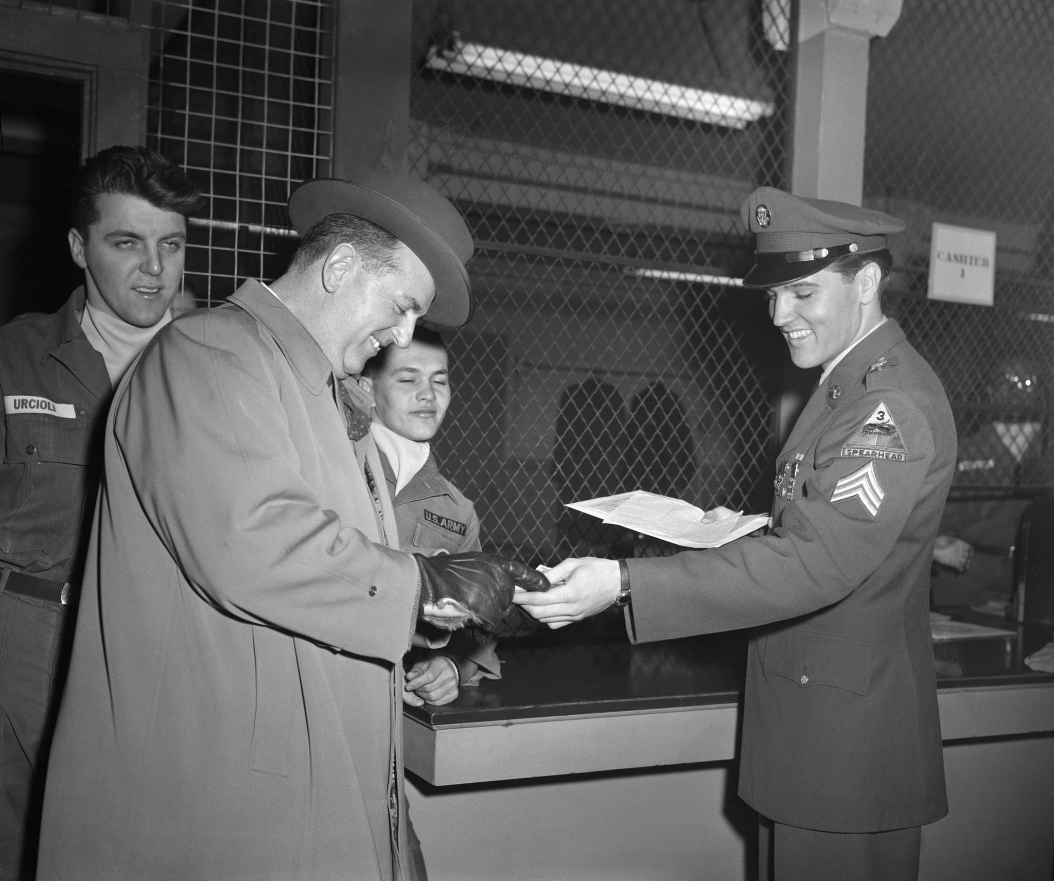 (Original Caption) 3/5/1960-Fort Dix, NJ- After being discharged from the US Army today, Elvis Presley (R) grins as he hands his mustering out pay to his business manager Colonel Tom Parker.
