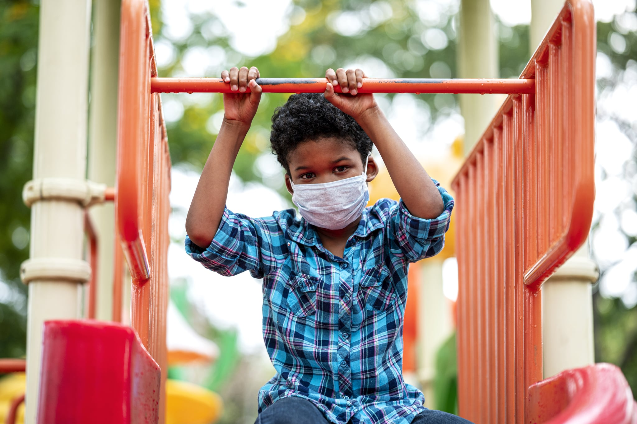 Lonely boy wearing protective face mask while playing at playground.