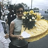 "An older woman carries a flower arrangement that says, ""We love you, Elvis."""