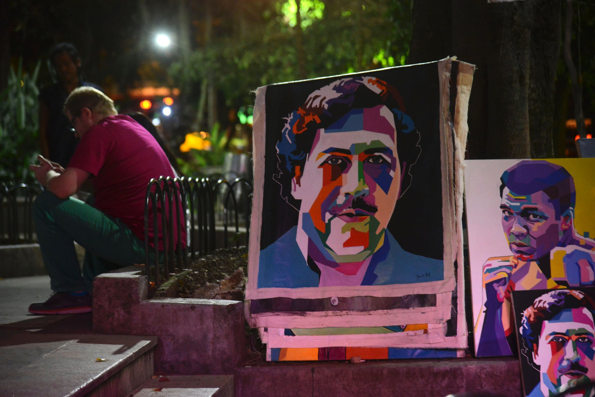 Paintings depicting late Colombian drug lord Pablo Escobar are on display at Lleras Park in  Medellin, Antioquia department, Colombia on July 21, 2016.The paintings are made by Colombian artist Wilson Rojas, who sells them by the equivalent of 120-130 dollars each. / AFP / RAUL ARBOLEDA        (Photo credit should read RAUL ARBOLEDA/AFP via Getty Images)