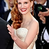 Jessica exudes Old Hollywood glamour in her embellished ivory Giorgio Armani gown and Chopard earrings.