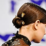 From the back, we can see that Millie's sleek, twisted bun is held up by gold-and-pearl hairpins.