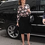 On day one, Linda tucked a floral blouse into a pleated black knee-length skirt, then added much-needed funk via round shades and a cool black shoulder bag. Top this look off with a blazer to sharpen things up.