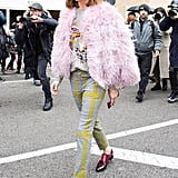 Making her way to the Ralph Lauren show, Olivia wore a sweater and trousers by the brand. She topped the look off with a Cinq á Sept marabou jacket and Satoni loafers.