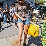 A ladylike sheer blouse and heeled ankle boots dressed up Sienna Miller's shorts to give them a more grown-up feel.