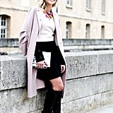 Bright statement jewels and statement boots — not to mention a metallic clutch — gave her feminine look a serious taste of the trends.