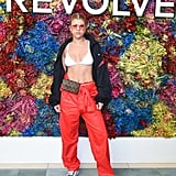 Sofia Richie wearing red trousers, a bikini top, and a Louis Vuitton waist bag at the Revolve festival.