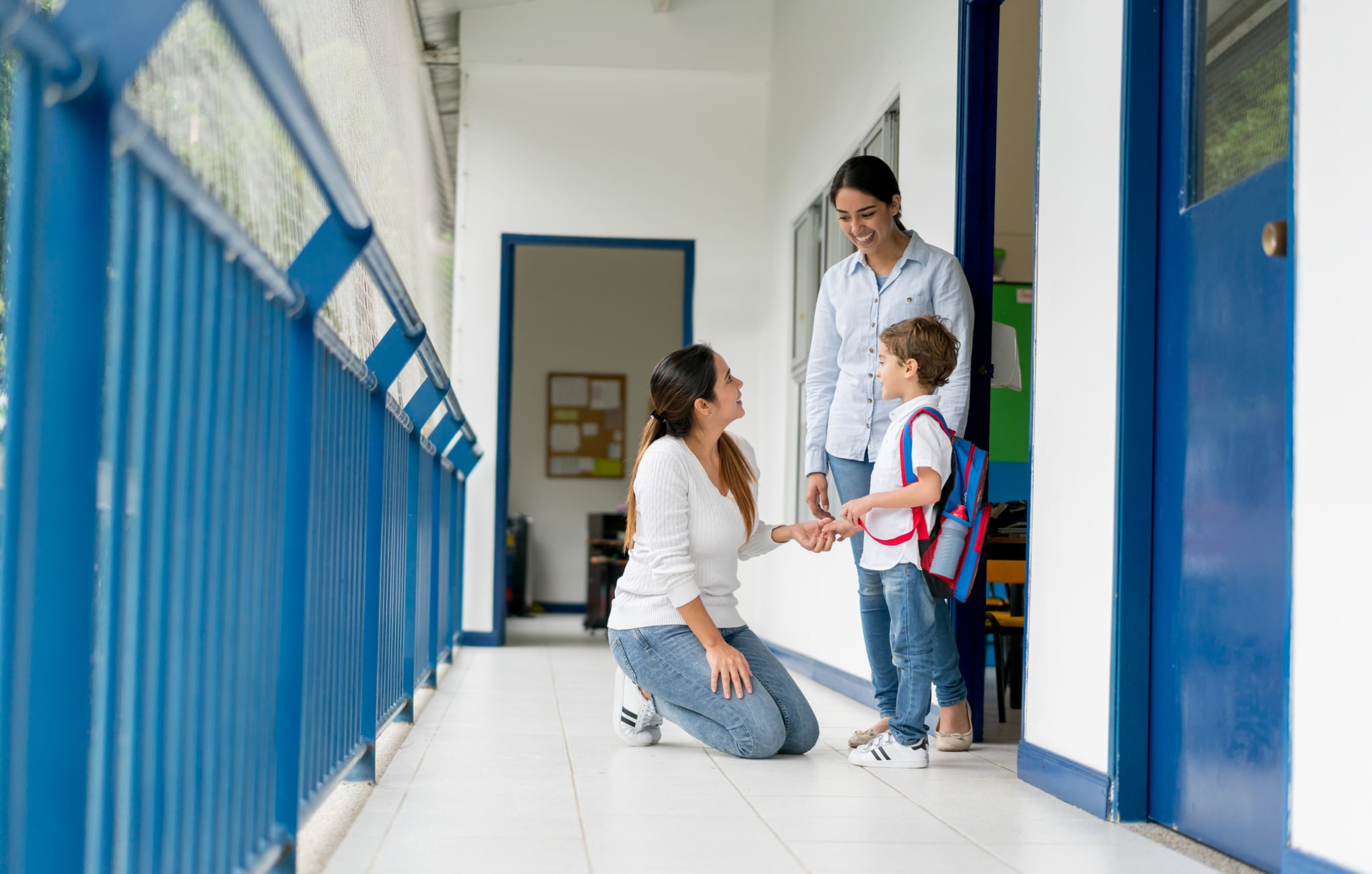 Portrait of a mother picking up her kid from school and talking to the teacher while looking happy - education concepts