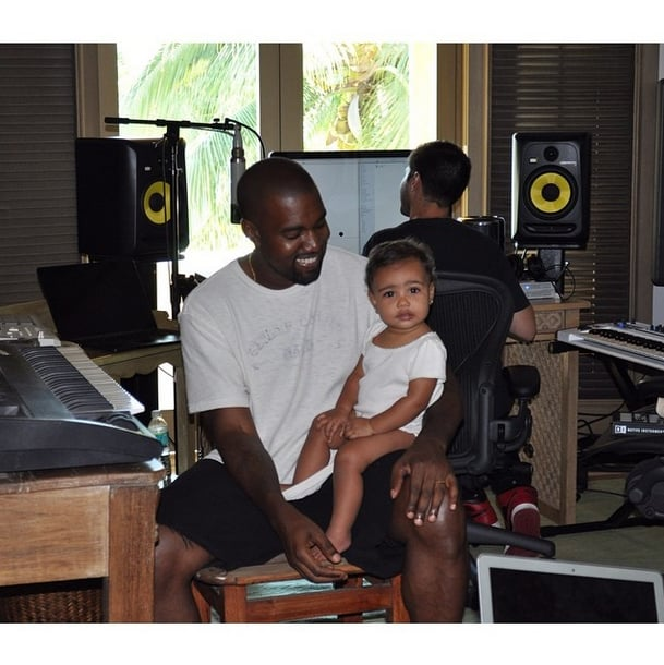 "Kim shared this sweet photo of Kanye and North in August 2014, with the caption ""#bringyourdaughtertoworkday."""