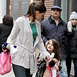 Suri Cruise carried two dolls in her arms.