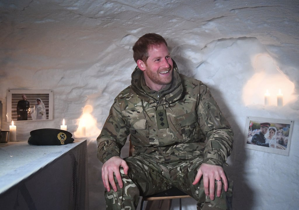 """We hope Meghan's ready to get the kettle on, because when Prince Harry gets home from work, he's going to need warming up. The prince spent Valentine's Day in freezing temperatures, as he paid a visit 200 miles inside the Arctic Circle in northern Norway. Harry's visit was to celebrate the 50th anniversary of Exercise Clockwork, an elite training exercise that teaches military personnel how to operate, fight, and survive in extreme cold weather. Harry — who took over the role of Captain General of the Royal Marines in 2017 — arrived at the base in uniform, fitting right in as he met troops, and received a briefing on the operation.  During his visit, Harry also checked out Quincey Shelter, a version of an igloo that is dug out and used in emergencies; the troops surprised Harry by decorating the inside of the igloo with candles, romantic music, and framed photos of him and Meghan on their wedding day. """"You weirdos! Nice,"""" Harry remarked with a laugh. He also called it """"homey"""" and """"romantic,"""" adding, """"It's very kind of you to invite me into your private, err, shrine."""" See all the photos from his trip ahead.      Related:                                                                                                           Oops, They Did It Again! Harry and Meghan Make Yet Another Glamorous Appearance"""