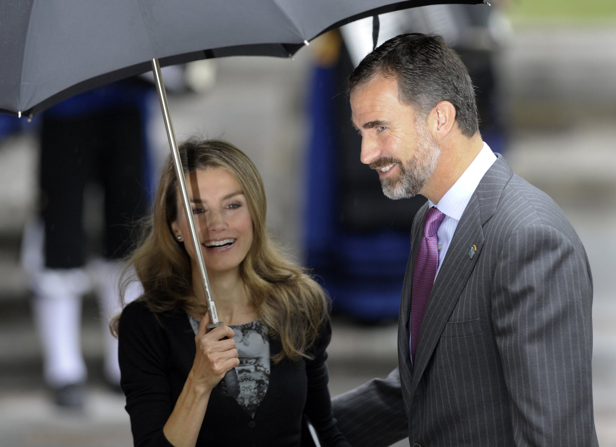 Princess Letizia and Prince Felipe shared a laugh on a rainy day in October 2013.