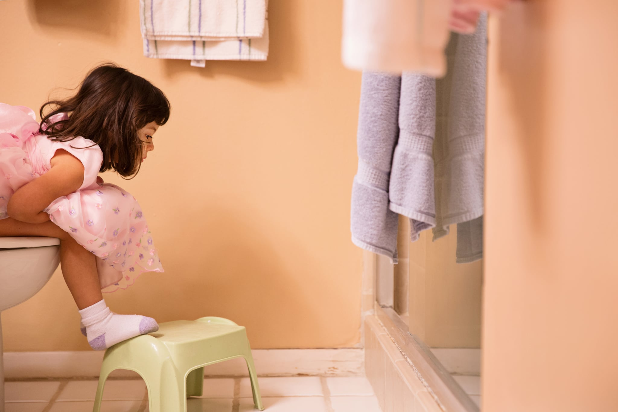 A toddler girl sits on the potty wearing her dress and socks.
