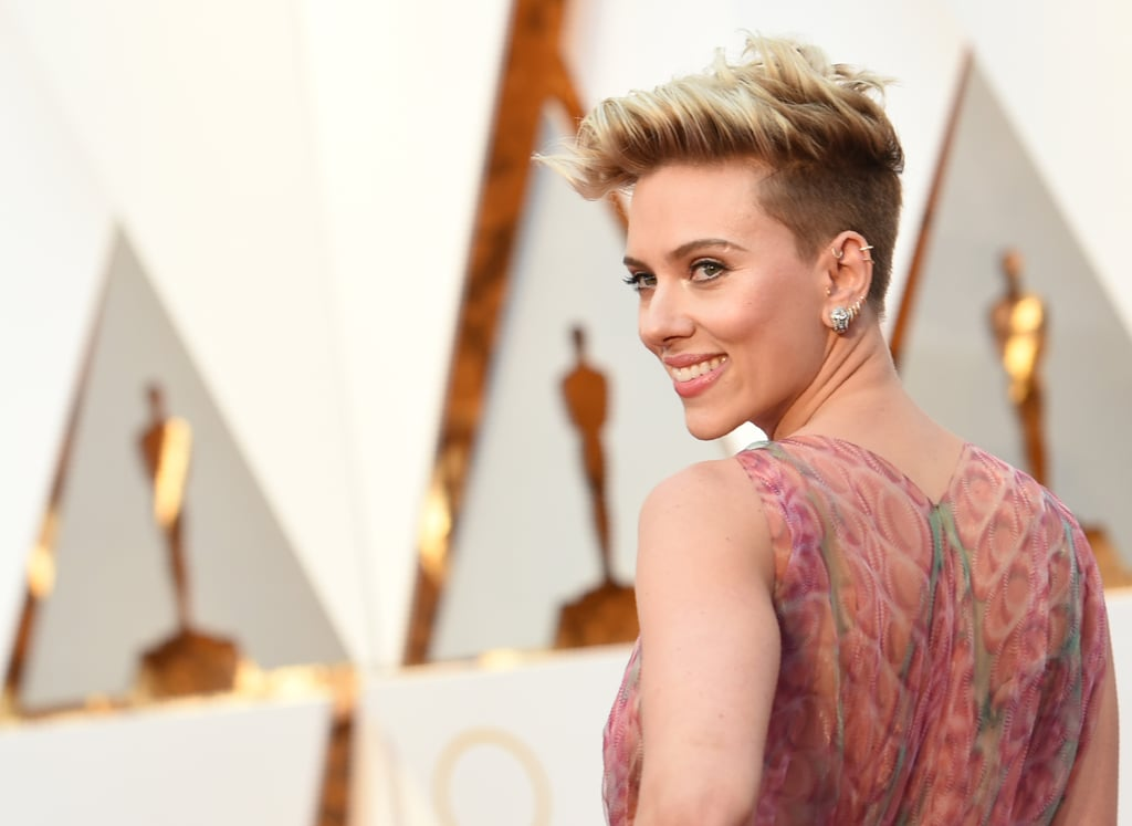 When Scarlett Johansson took to the red carpet at the Oscars, we were immediately drawn to her gorgeous hairstyle and shimmery makeup. Hairstylist Jenny Cho created Scarlett's edgy look by prepping her strands with Suave Professionals Honey Infusion 10-in-1 Leave-In Conditioning Cream. For that touchable texture, Jenny spritzed in some sea salt spray before blow drying her hair and using a flat iron to lift her strands from the roots and create those effortless waves. As for makeup, dewy, rosy cheeks and perfectly highlighted cheekbones paired together for one seriously glowing look. Her pink lips matched the hue of her flowy gown. The deep side cuts of her dress allowed a rose tattoo on her ribcage to peek out as she posed for photos. The actress kept her eye makeup clean and simple — perfect for everyday wear. Read on to see Scarlett's rocker-chic style from every angle.