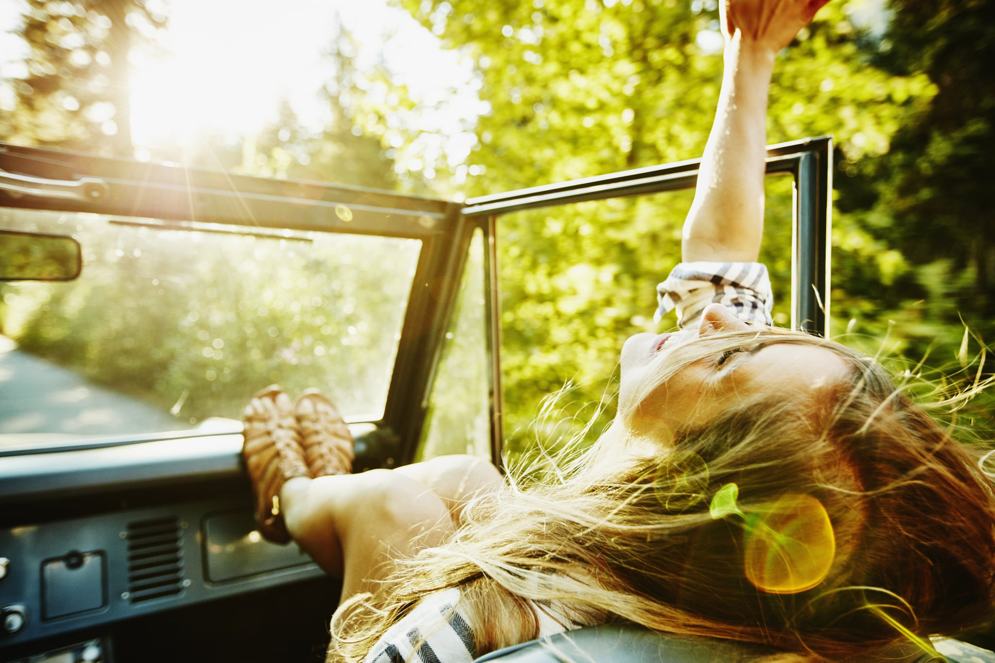 Woman riding in passenger seat of convertible with head back and arm raised towards sky