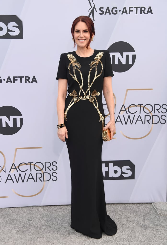 """Megan Mullally's gorgeous gowns for the 2019 SAG Awards were only a click away! The host of Sunday's awards show bought each of her three dresses online, instead of picking through options in stores. She started the night by walking the red carpet in a short-sleeved black Alexander McQueen gown with gold detailing, which she paired with a matching metallic gold clutch.  """"This is mine, I bought this online. It's Alexander McQueen. I'm wearing two different dresses in the show that I bought online,"""" Megan told Entertainment Tonight. She later slipped into a formfitting ruby red glitter gown, and then changed one last time into a breezy, bishop sleeve dress. See all of Megan's online-shopping treasures ahead — we love an efficient queen!"""
