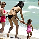 Happy mom Adriana Lima on the beach in a bikini.
