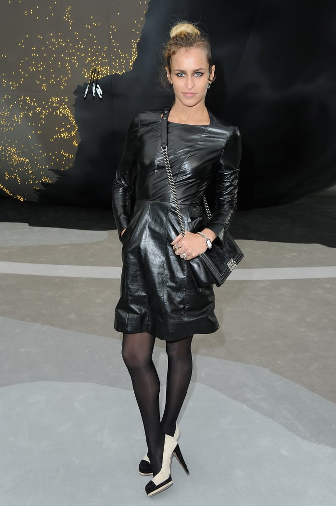 Alice Dellal, the face of Chanel Boy handbags, attended the brand's Fall 2013 runway show in an artfully draped leather dress — she layered up against the Paris chill with black tights.